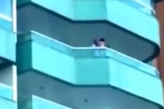 Terrifying moment toddler dangles from fifth floor balcony (video)