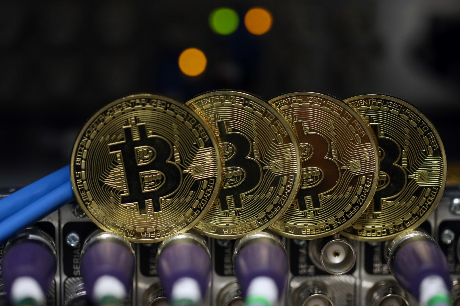 Bitcoins sit on coaxial cables inside a communications room at an office in this arranged photograph in London, U.K., on Tuesday, Sept. 5, 2017. Bitcoin steadied after its biggest drop since June as investors and speculators reappraised the outlook for initial coin offerings. Photographer: Chris Ratcliffe/Bloomberg via Getty Images