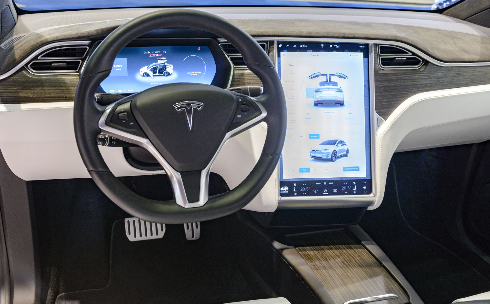 Brussels, Belgium - January 13, 2017: Luxurious interior on a Tesla Model X P90D full electric luxury crossover SUV car with a large touch screen and dashboard screen. The car is fitted with leather seats and aluminium details. The Model X uses falcon wing doors for access to the second and third row seats. The car is displayed on a motor show stand, with lights reflecting off of the body.