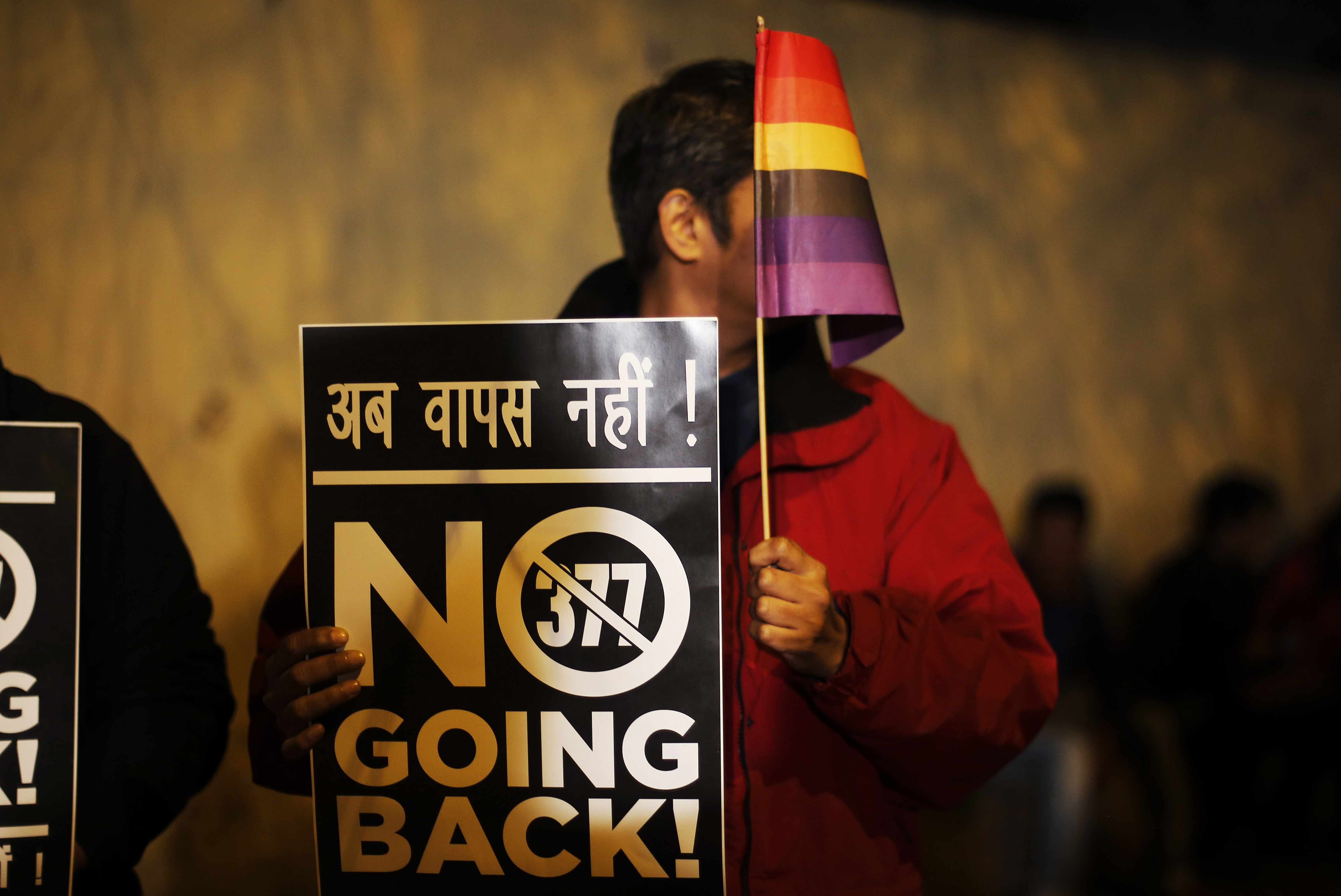 Associated Press An Indian Gay Rights Activist Holds Up A Placard And A  Flag During A Protest Against A Recent Supreme Court Verdict That Upheld  Section 377