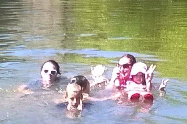 Does this photo of a family swimming show the ghost of a child who drowned 100 years ago?