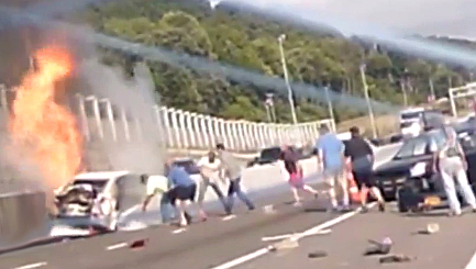 Dramatic moment strangers rescue woman from burning car