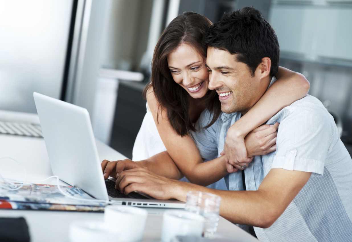 Smiling, young couple surfing the internet on a laptop