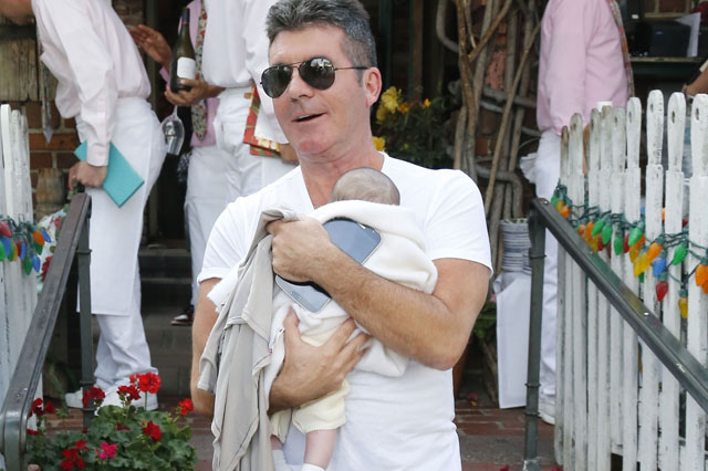 Simon Cowell cuddles baby Eric to his chest as he leaves Hollywood restaurant