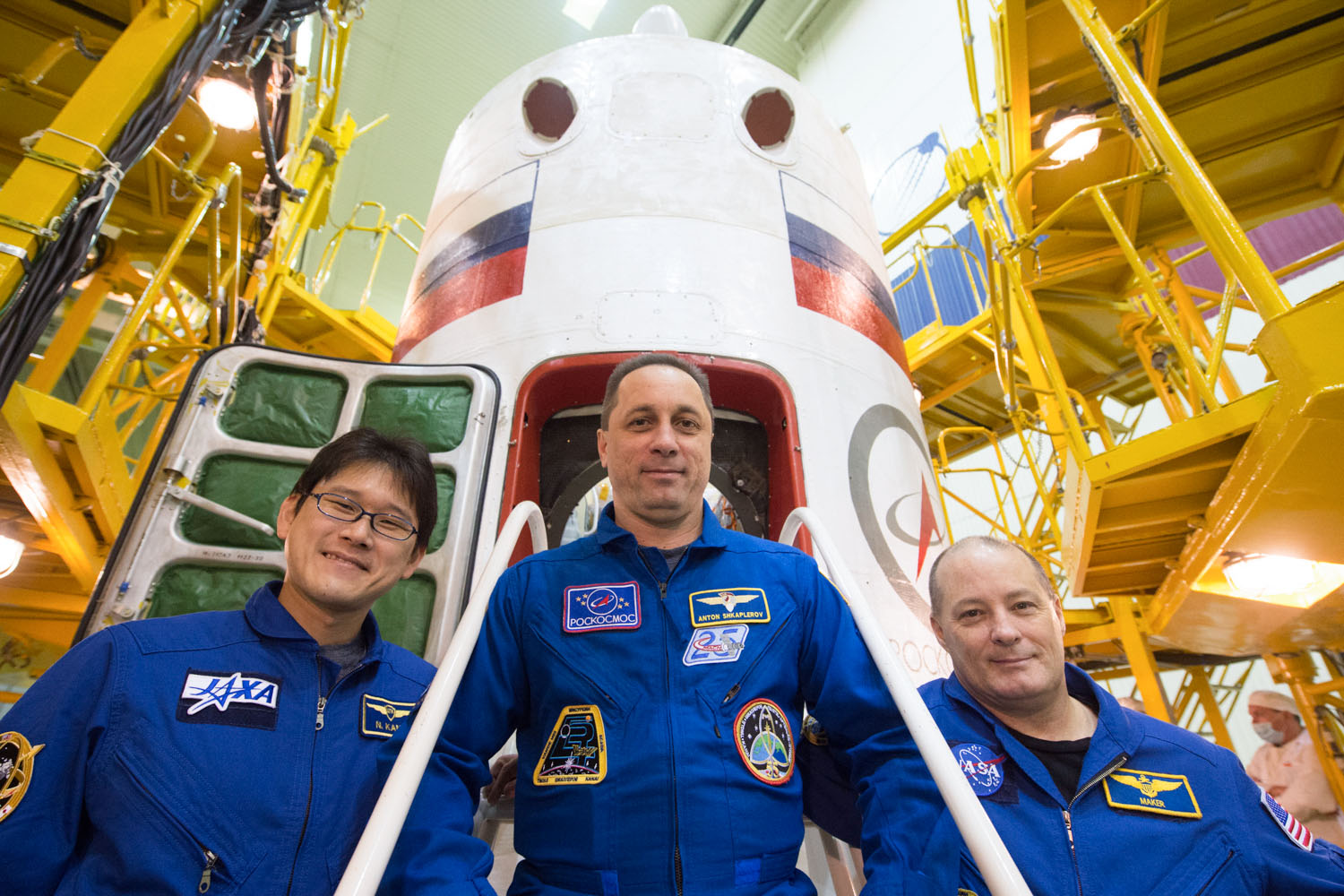 jsc2017e138117 - At the Integration Facility at the Baikonur Cosmodrome in Kazakhstan, the Expedition 54-55 prime crewmembers pose for pictures Dec. 13 in front of the Soyuz MS-07 spacecraft during pre-launch training. Norishige Kanai of the Japan Aerospace Exploration Agency (JAXA), Anton Shkaplerov of the Russian Federal Space Agency (Roscosmos, center) and Scott Tingle of NASA (right) will launch Dec. 17 on the Soyuz MS-07 vehicle for a five month mission on the International Space Station...Andrey Shelepin/Gagarin Cosmonaut Training Center.