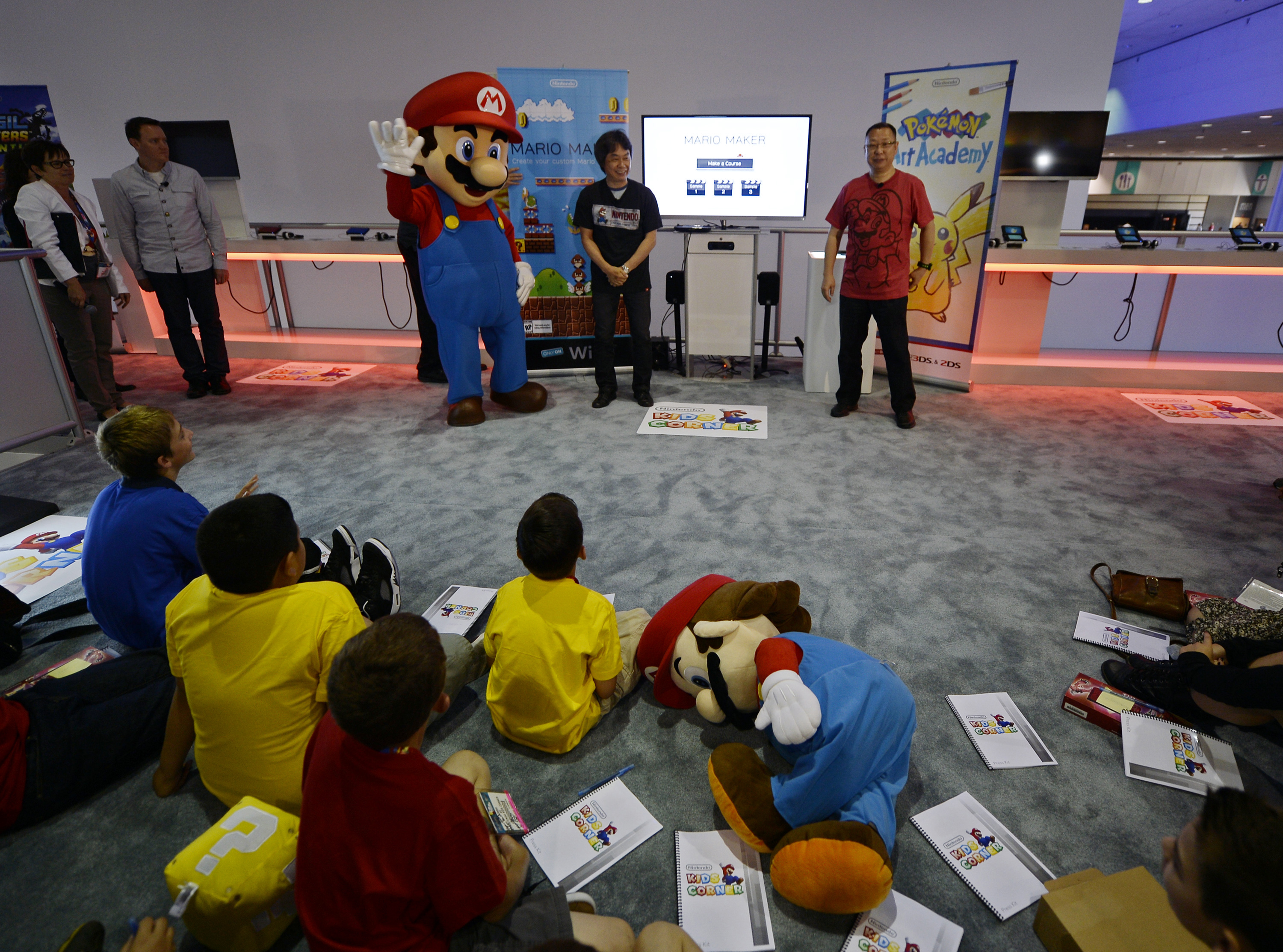 "Shigeru Miyamoto (C), Nintendo's senior managing director and general manager of its Entertainment Analysis and Development division, and Takashi Tezuka (R), executive officer of Nintendo's Entertainment Analysis and Development division, together with Nintendo's character Mario (L), introduce a new game ""Mario Maker"" while a small group of children look on during a news conference at the 2014 Electronic Entertainment Expo, known as E3, in Los Angeles, California June 11, 2014.  REUTERS/Kevork Djansezian  (UNITED STATES - Tags: SCIENCE TECHNOLOGY SOCIETY BUSINESS TPX IMAGES OF THE DAY)"