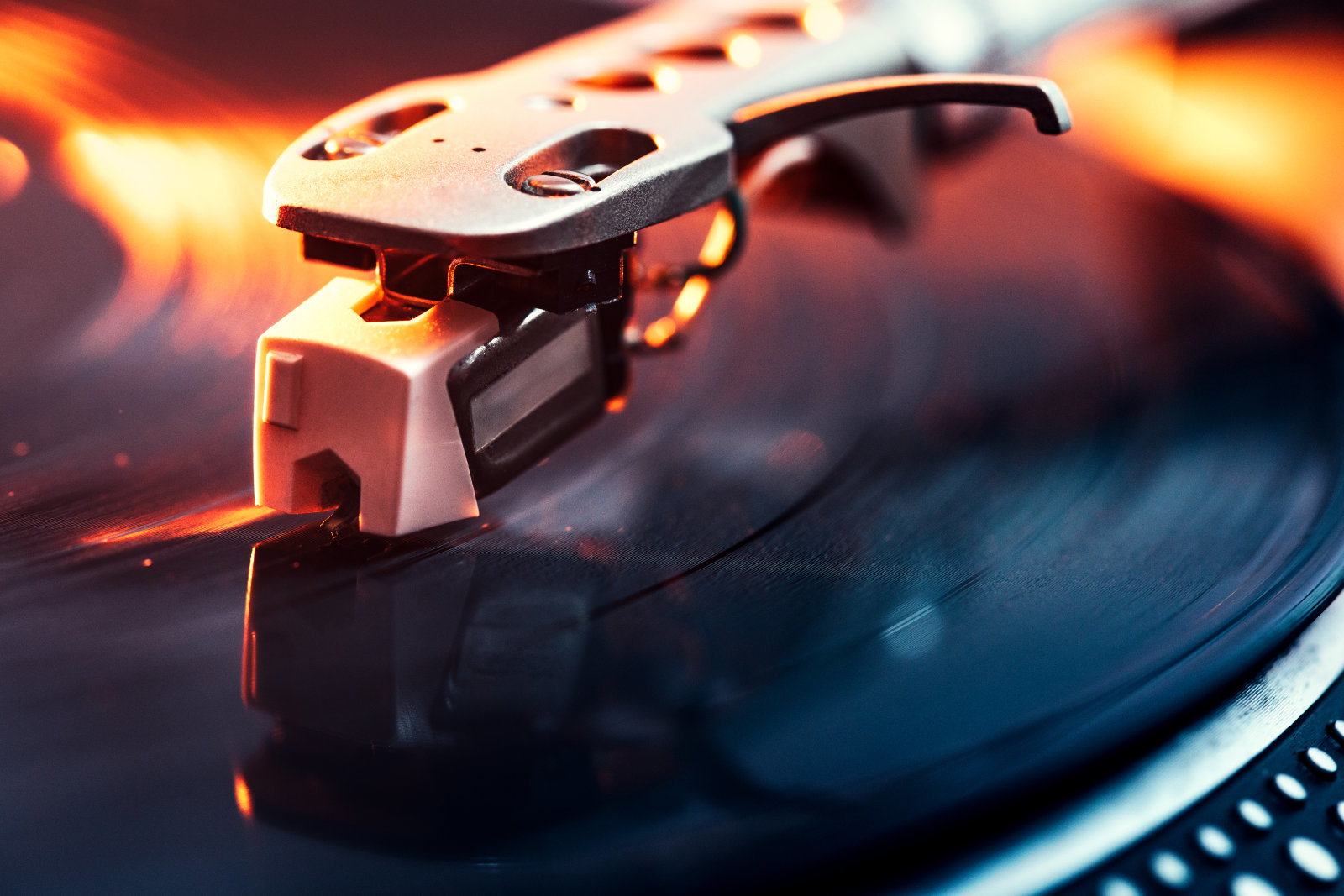 A close up shot of a running record player spinning out some music, dramatically lit with orange light.  Horizontal with copy space.