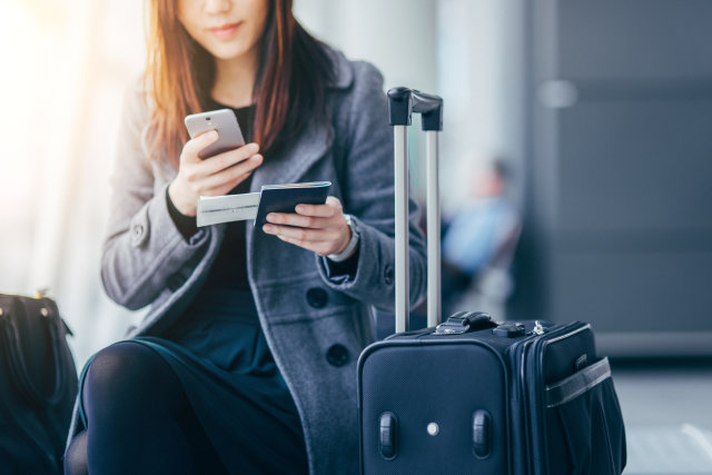 Woman holding smartphone and passport at airport