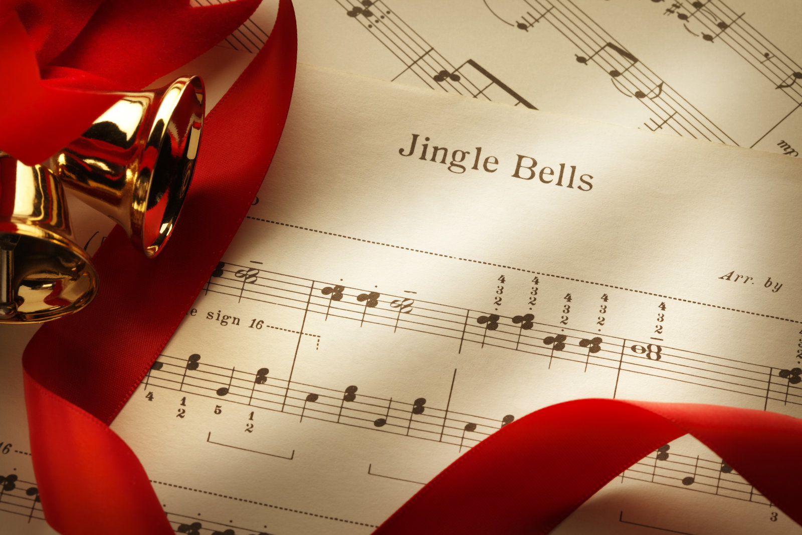 Several Christmas bells and red ribbon on the sheet music from the Christmas classic, Jingle Bells.
