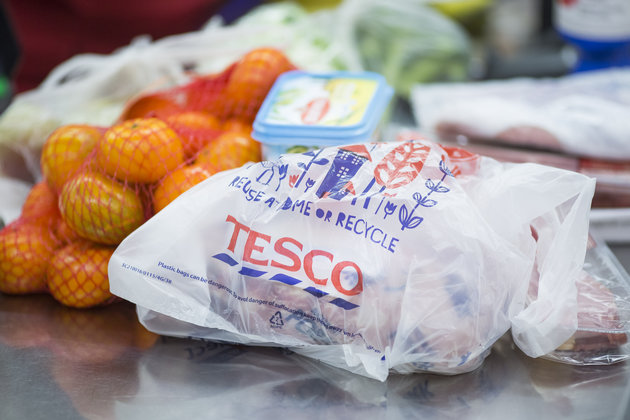 A Tesco-branded plastic shopping bag sits on a check-out desk inside a Tesco supermarket, operated by Tesco Plc, in London, U.K., on Monday, April 20, 2015. Tesco's April 22 results will serve as a reminder of the scale of the task still facing new Chief Executive Officer Dave Lewis after his decision to close dozens of stores, cancel some openings, consolidate head offices and cut prices on hundreds of branded goods. Photographer: Jason Alden/Bloomberg via Getty Images