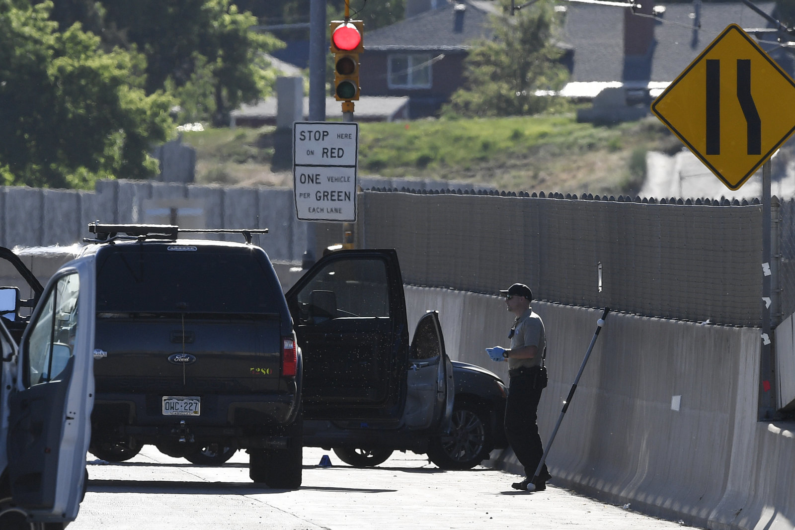DENVER, CO - JUNE 01: A Denver crime scene investigator on scene of a fatal shooting which an Uber driver (car into the barrier, far right) allegedly shot and killed a passenger early Friday morning on I-25 southbound at University Blvd June 01, 2018. (Photo by Andy Cross/The Denver Post via Getty Images)