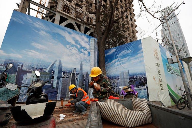 Trabalhadores almoçam em canteiro de obras no Distrito Central de Negócios de Pequim, diante de um mural que retrata o skyline da capital chinesa.
