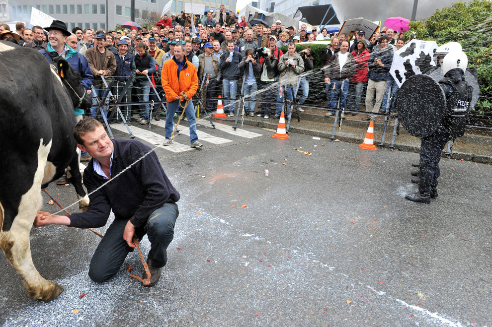 manliest photos on the internet, funny manly images, belgian farmer squirts milk at police