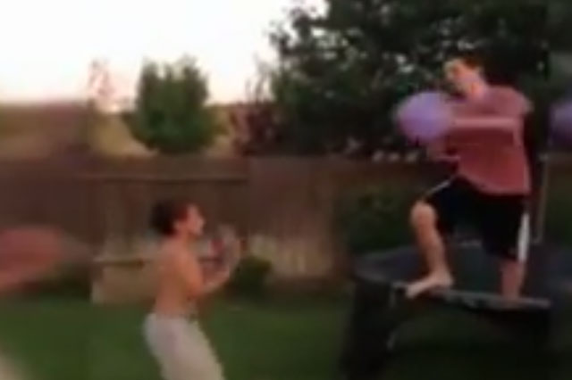 Laughing dad films son being knocked out cold in water balloon fight (video)