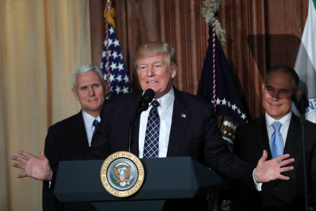 "U.S. President Donald Trump speaks between Vice President Mike Pence (L) and EPA Administrator Scott Pruitt prior to signing an executive order on ""Energy Independence,"" eliminating Obama-era climate change regulations, during an event at the Environmental Protection Agency (EPA) headquarters in Washington, U.S., March 28, 2017. REUTERS/Carlos Barria"