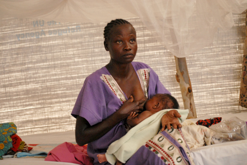 Onesta, from South Sudan, breastfeeds her two month-old daughter Diana in a sweltering refugee tent.