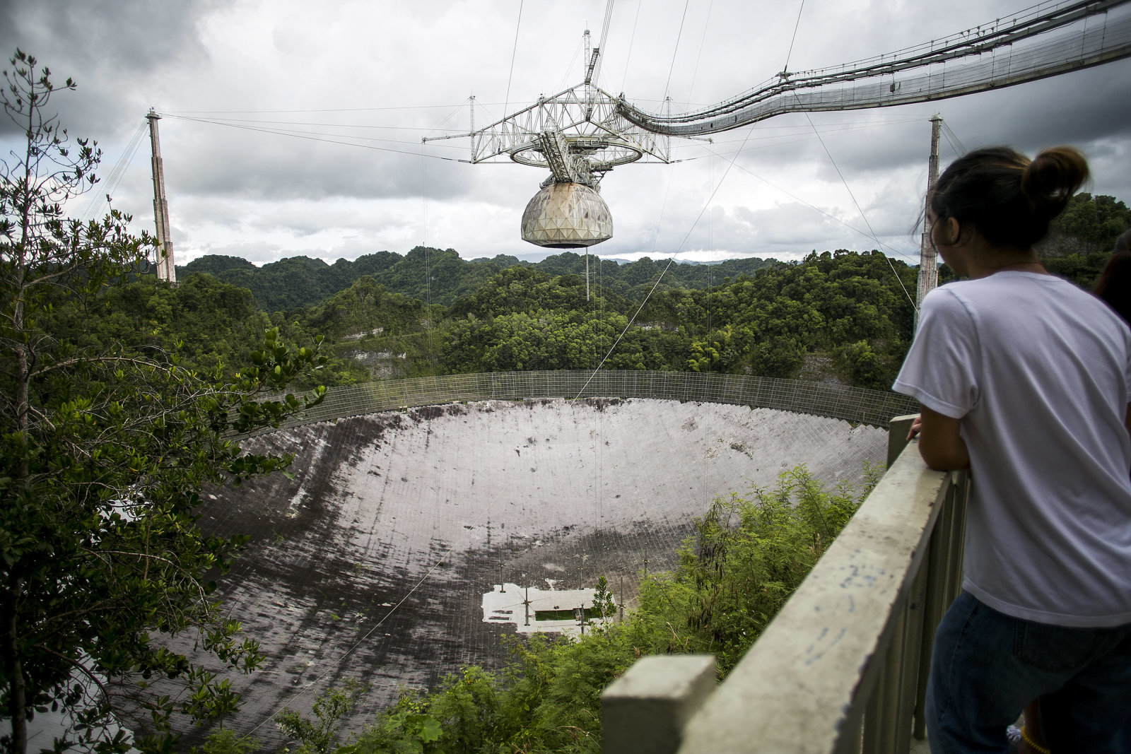 A visitor views the world's largest single dish radio telescope at the Arecibo Observatory in Arecibo, Puerto Rico, on Friday, Aug. 25, 2017. Over the years, Puerto Rico has wooed visitors and investors with beaches, sun, tax breaks and splashy public works. Now the Caribbean island wants to add an outpost of Chinese culture, complete with graceful pavilions and regional cuisine. Photographer: Xavier Garcia/Bloomberg via Getty Images