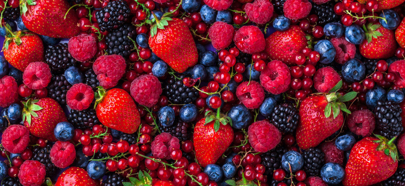 Forest fruit berries overhead assorted mix in studio on dark background with raspberries, blackberries, blueberries, red currant.