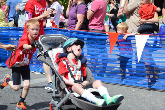He ain't heavy: Boy, 8, completes mini triathlon with severely disabled little brother in tow