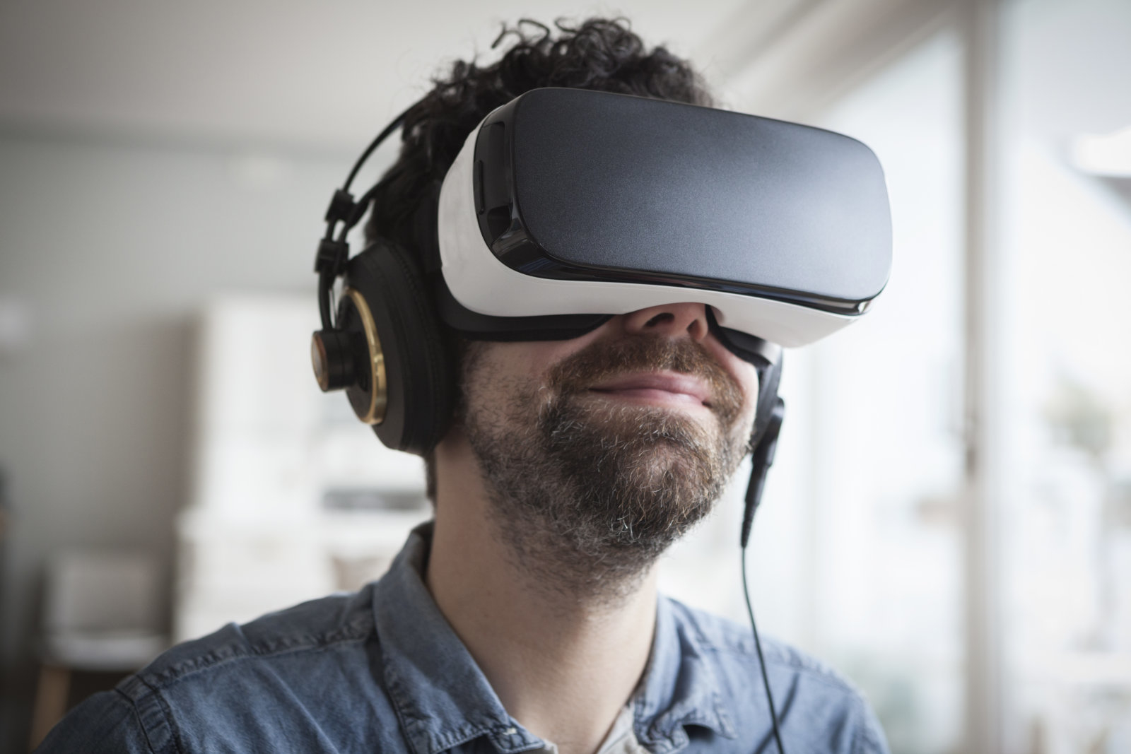 Smiling man wearing Virtual Reality Glasses and headphones