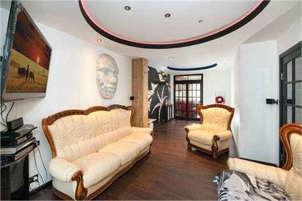 One of the living rooms, with silver face on the wall.