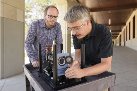Assistant prof. Gordon Wetzstein and postdoctoral scholar Donald Dansereau with a prototype of the monocentric camera that captured the first single-lens panoramic light fields.