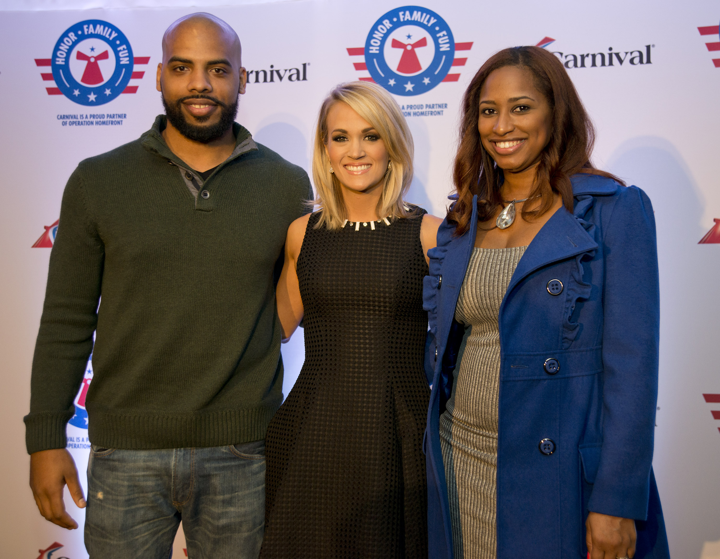 Carrie Underwood, center, poses with U.S. Navy Petty Officer Andrew Friedlander, left, and his wife Bryanne Friedlander, right, following a news conference Thursday, Jan. 28, 2016, in Jacksonville, Fla. The conference was staged to announce a new  partnership between Underwood, Operation Homefront and Carnival Cruise Line to support U.S. military families. The effort between the three entities is to raise funds through a series of projects during Underwood's concert tour and aboard Carnival's ships as well as the company's website. FOR EDITORIAL USE ONLY (Andy Newman/Carnival Cruise Line/HO)