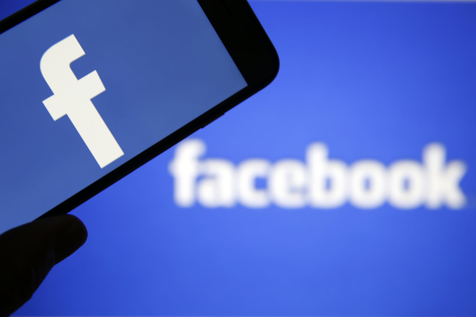 PARIS, FRANCE - MARCH 20:  In this photo illustration the Facebook logo is seen on the screen of an iPhone in front of a computer screen showing a Facebook logo on March 20, 2018 in Paris, France. Cambridge Analytica is accused of collecting the personal information of 50 million users of the Facebook social network without their consent and would have used it to develop software to predict and influence voter voting during the campaign American election according to the New York Times and the Guardian. Facebook share price fell by more than 5% Monday shortly after the opening of Wall Street.  (Photo Illustration by Chesnot/Getty Images)