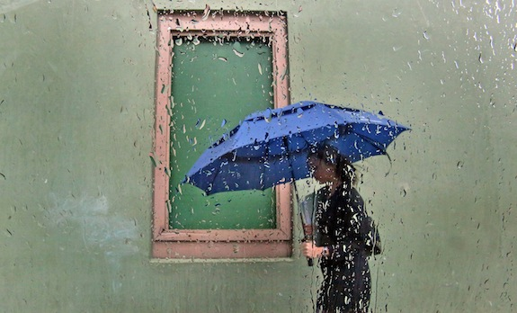 Looking through a rain-covered window on a chilly, dreary day, a pedestrian passes by a boarded up window on West Washington Street in downtown Orlando, Fla., Thursday, March 6, 2014. (Red Huber/Orlando Sentinel/MCT)