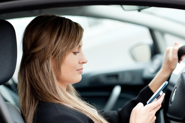 Beautiful businesswoman sending a text while driving to work