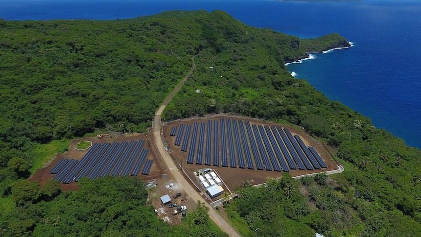 Feld mit Solarzellen an bewaldeter Küste