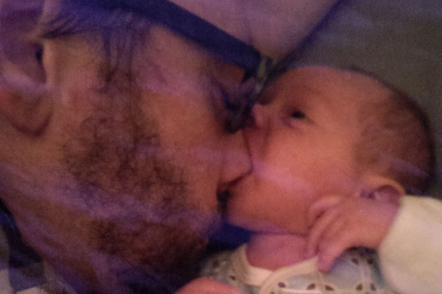 baby sucking dad's nose