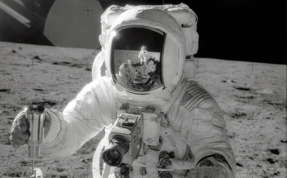 Astronaut Alan L. Bean, Lunar Module pilot for the Apollo 12 lunar landing mission, holds a Special Environmental Sample Container filled with lunar soil collected during the extravehicular activity (EVA) in which Astronauts Charles Conrad Jr., commander, and Bean participated. Connrad, who took this picture, is reflected in the helmet visor of the Lunar Module pilot.