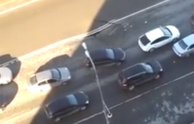 Screencap of a video showing a sinkhole opening up on a Russian road.