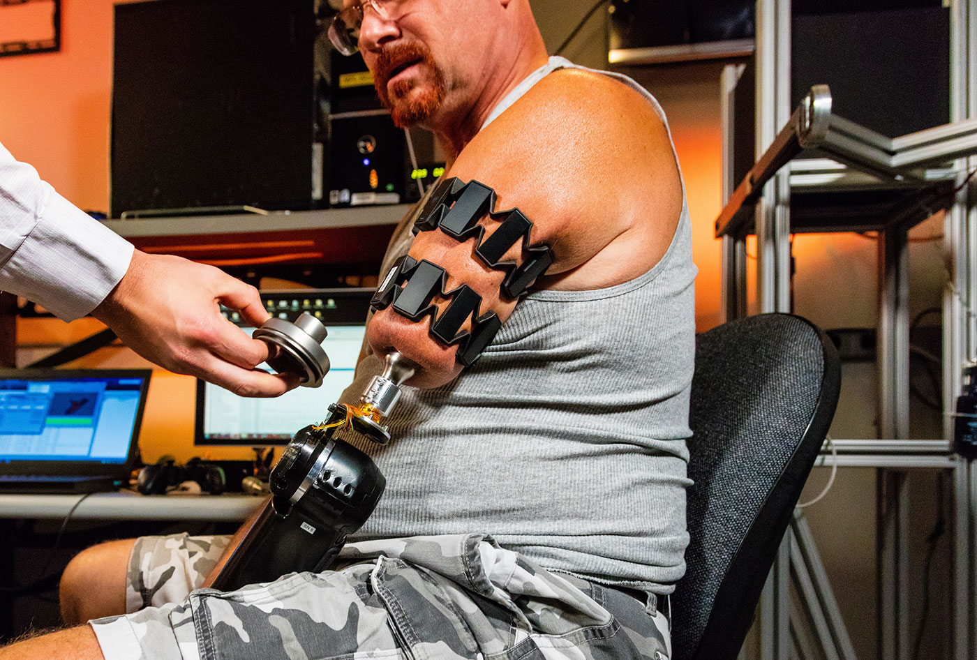 johnny matheny, an amputee, wearing moo armbands and working with his prosthetic arm