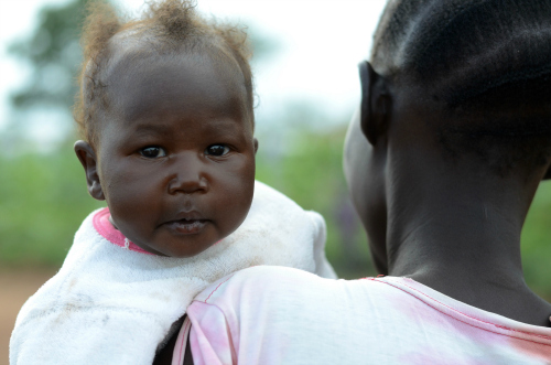 A baby girl looks over a woman's shoulder