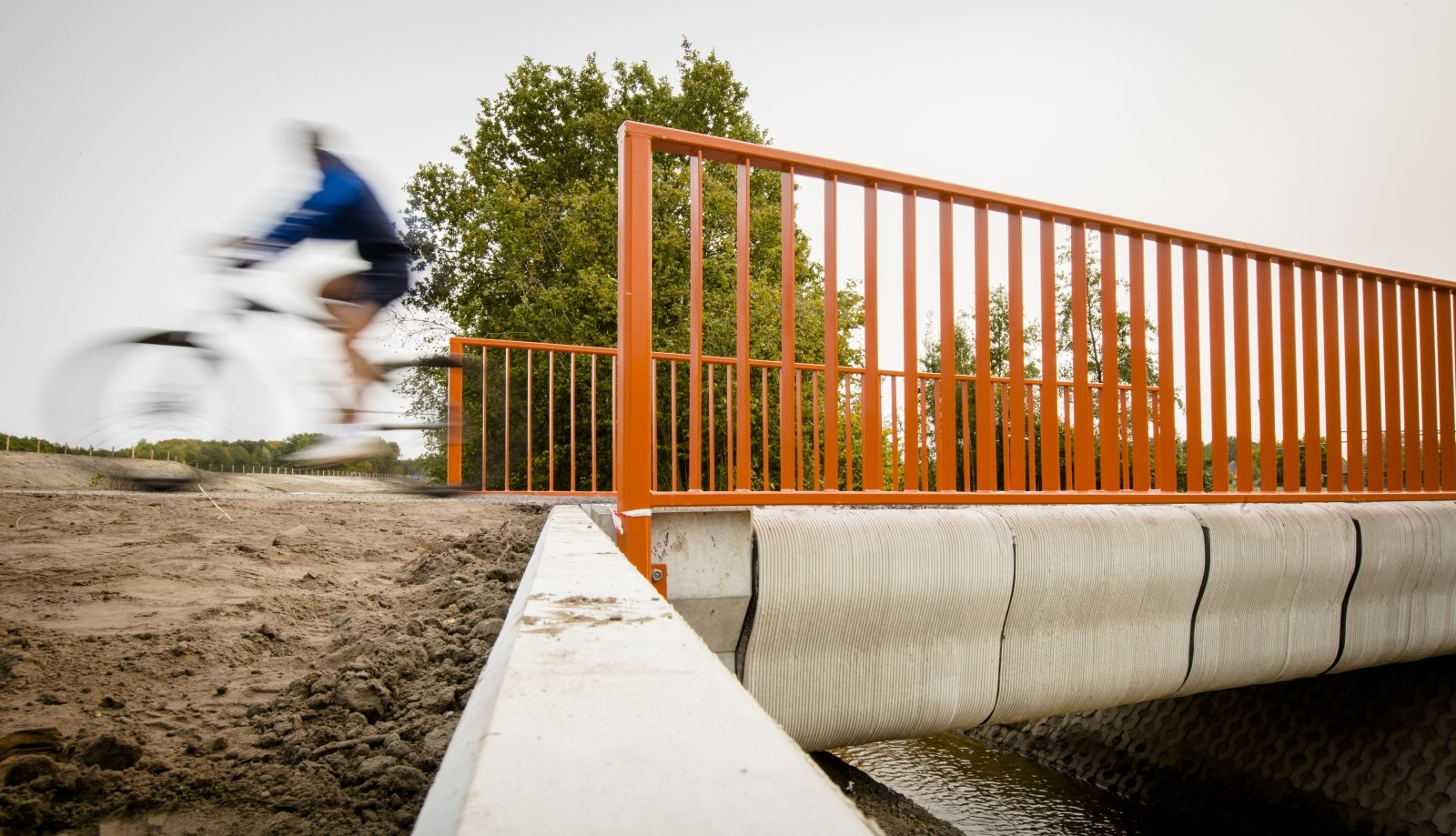 A Cyclist rides over what has been named as the world's first 3-D printed concrete bridge after its opening in Gemert, The Netherlands on October 17, 2017.   Dutch officials toasted the opening of what is being dubbed as the world's first 3D-printed concrete bridge, which is primarily meant to be used by cyclists.There was applause as officials wearing hard hats and workmen's jackets rode over the bridge on their bikes at the inauguration in the southeastern town of Gemert.  / AFP PHOTO / Bart Maat        (Photo credit should read BART MAAT/AFP/Getty Images)