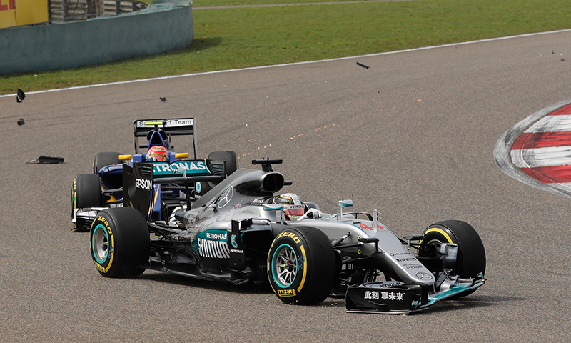 Debris flies from the front wing of the car of Mercedes driver Lewis Hamilton of Britain after he makes contact with other driver during the Chinese Formula One Grand Prix at Shanghai International Circuit.