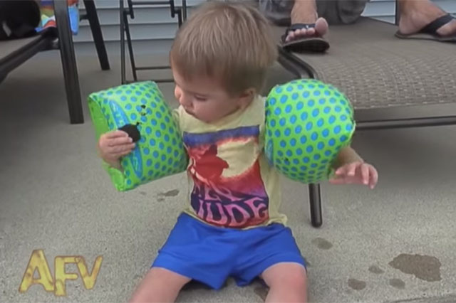 toddler in armbands tries to eat cookie