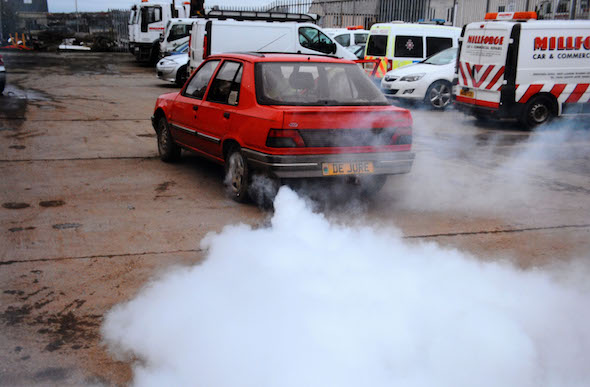 "A speeding driver who deployed a James Bond-style smokescreen device in a bid to shake off police has been spared jail.  Simon Chaplin, 62, rigged a bucket of diesel, a pump and pipes, behind the passenger seat of his Peugeot 309 to produce ""colossal"" amounts of grey smoke from his exhaust.  A court heard ""eccentric"" Chaplin activated the device when a policeman attempted to pull him over for speeding and covered the carriageway with fumes.  Chaplin tried to evade the officer's flashing blue lights but the policeman was simply able to follow the billowing plumes through country roads near Haverfordwest, Pembs.   Pictured here is the smokescreen in action  © WALES NEWS SERVICE"