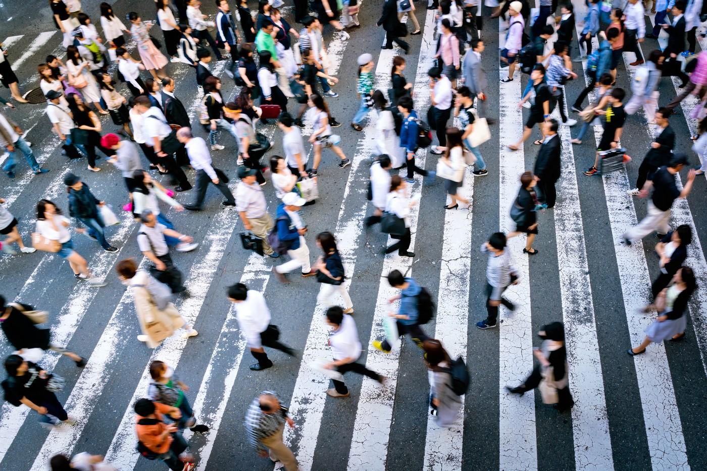 Many people cross the street on a zebra crossing in the Osaka