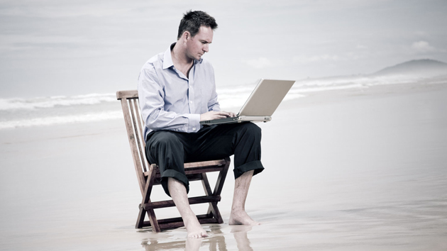 A concerned man checking his laptop on the beach