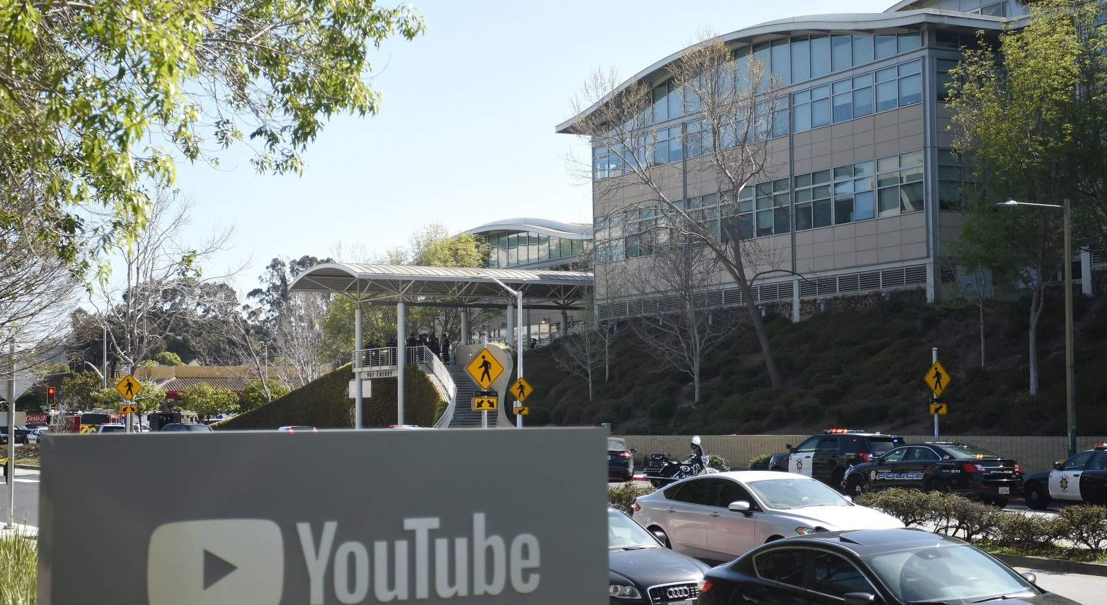 """YouTube's headquarters office is seen with police activity during an active shooter situation in San Bruno, California on April 03, 2018.                       Gunshots erupted at YouTube's offices in California Tuesday, sparking a panicked escape by employees and a massive police response, before the shooter -- a woman -- apparently committed suicide.Police said three people had been hospitalized with gunshot injuries following the shooting in the city of San Bruno, and that a female suspect was found dead at the scene. """"We have one subject who is deceased inside the building with a self-inflicted wound,"""" San Bruno Police Chief Ed Barberini told reporters. """"At this time, we believe it to be the shooter.""""  / AFP PHOTO / JOSH EDELSON        (Photo credit should read JOSH EDELSON/AFP/Getty Images)"""