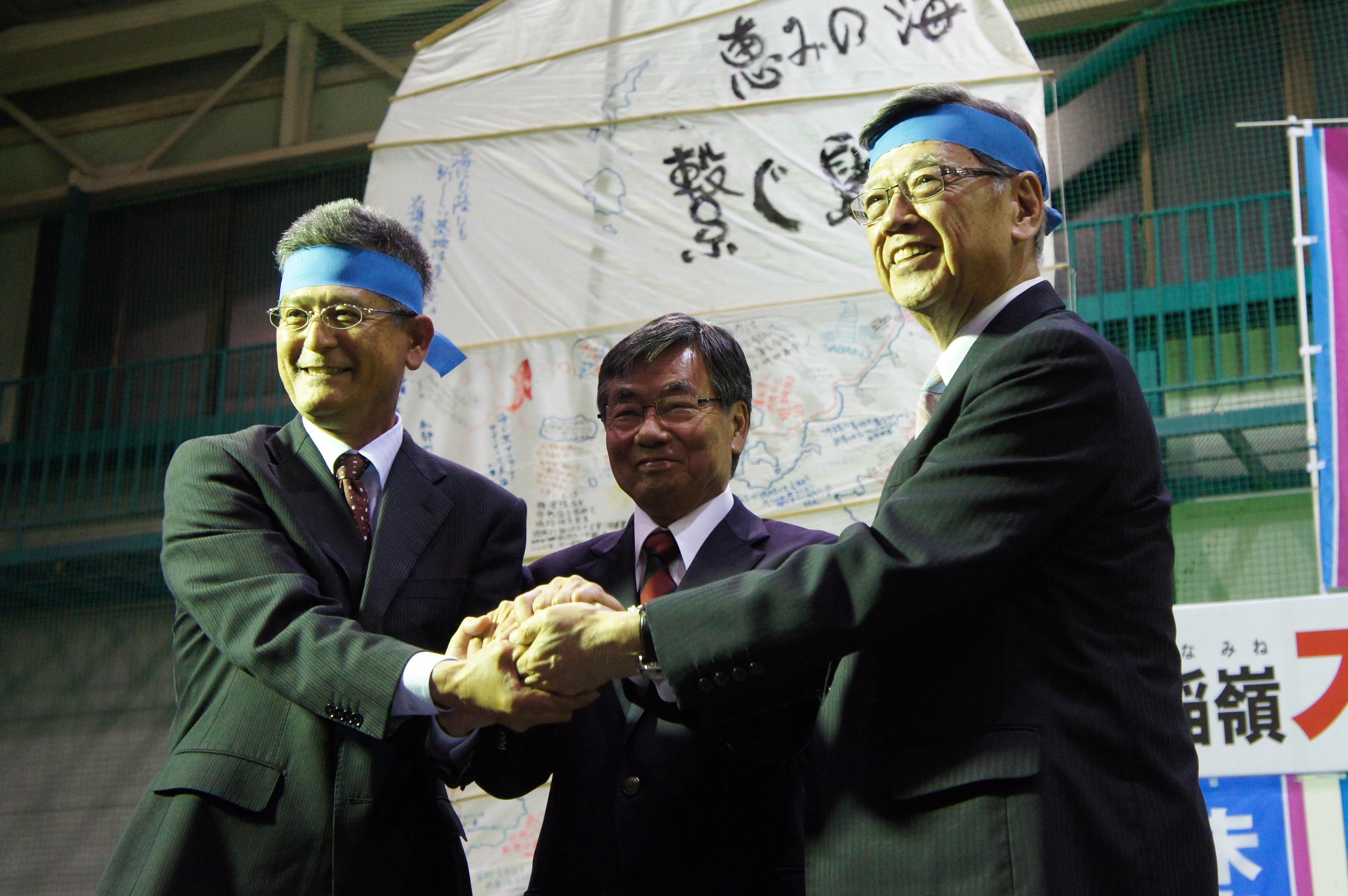 稲嶺進氏(中央)と手を結んだ翁長雄志県知事(右)と瑞慶覧長敏氏(左)=1月23日、名護市の21世紀の森屋内運動場