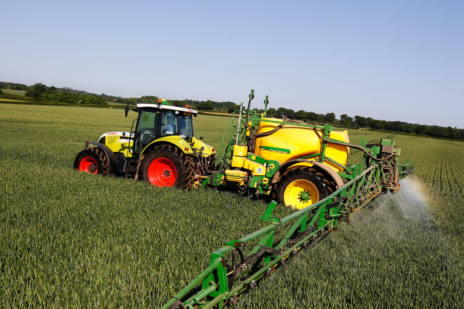A farmer drives a Claas KGaA Axion 640 tractor, fitted with a John Deere & Co. Greenstar 2600 terminal and John Deere & Co. 840i crop sprayer, through a field of wheat at Thrales End Farm near Harpenden, U.K., on Monday June 6, 2016. German chemical company Bayer AG cited the growth in such digitally assisted farming as a key reason for its $62 billion bid for Monsanto Co., which has become a leading provider of analytics used by growers. Photographer: Luke MacGregor/Bloomberg via Getty Images