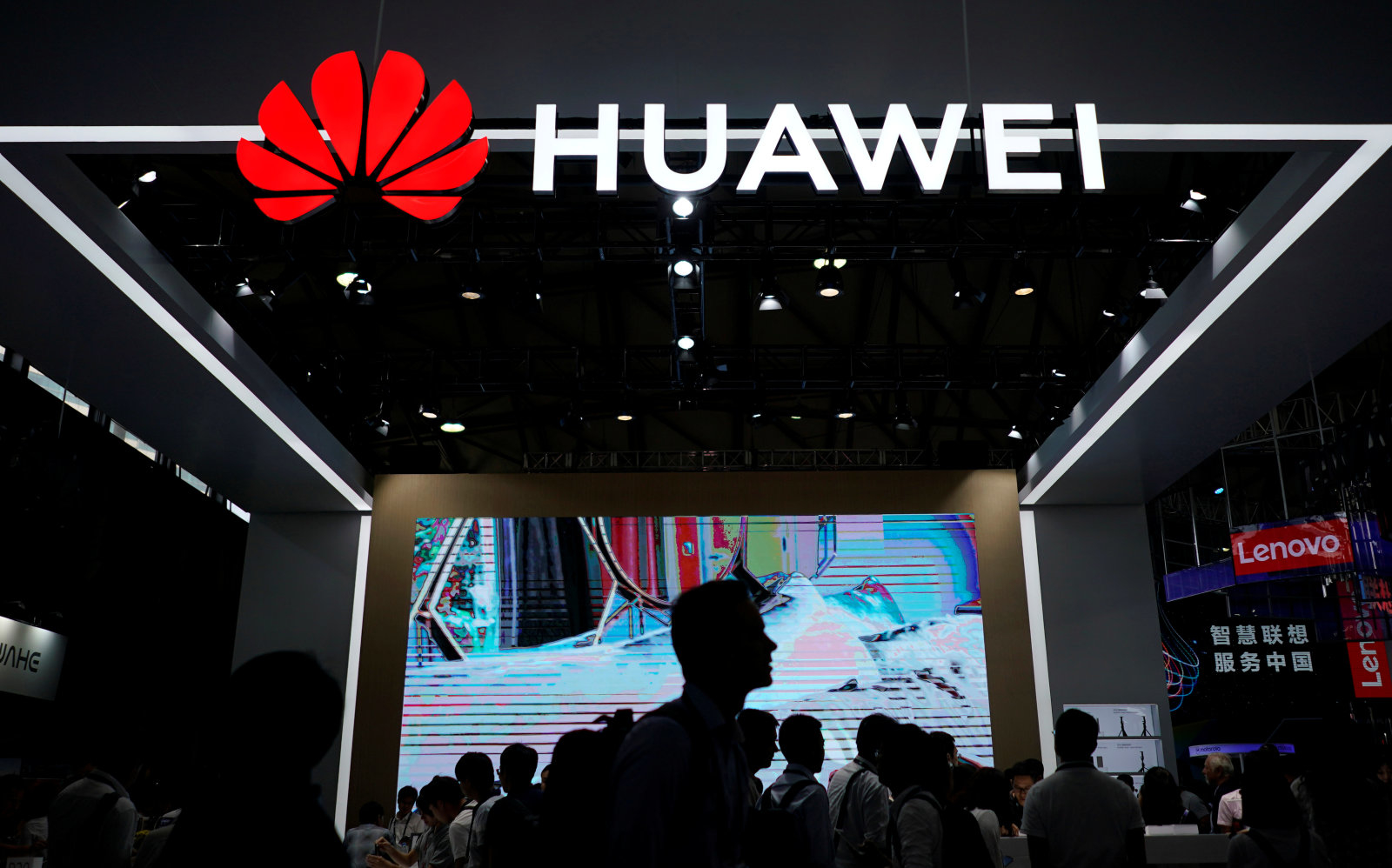 People walk past a sign board of Huawei at CES (Consumer Electronics Show) Asia 2018 in Shanghai, China June 14, 2018. REUTERS/Aly Song