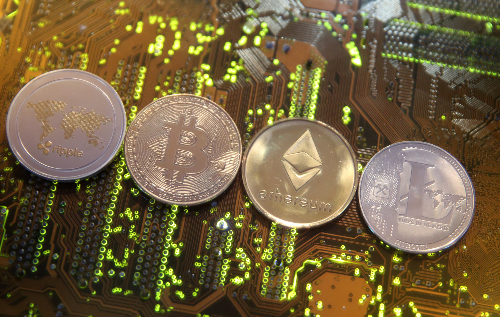 Representations of the Ripple, Bitcoin, Etherum and Litecoin virtual currencies are seen on a PC motherboard in this illustration picture, February 13, 2018. Picture is taken February 13, 2018. REUTERS/Dado Ruvic/Illustration