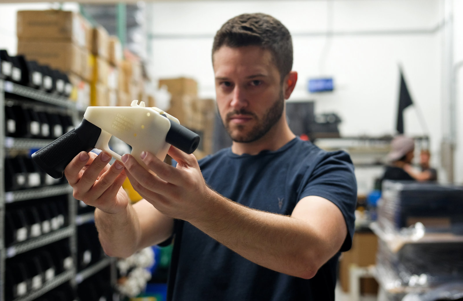 """TOPSHOT - Cody Wilson, owner of Defense Distributed company, holds a 3D printed gun, called the """"Liberator"""", in his factory in Austin, Texas on August 1, 2018. - The US """"crypto-anarchist"""" who caused panic this week by publishing online blueprints for 3D-printed firearms said Wednesday that whatever the outcome of a legal battle, he has already succeeded in his political goal of spreading the designs far and wide. A federal court judge blocked Texan Cody Wilson's website on Tuesday, July 31, 2018, by issuing a temporary injunction. (Photo by Kelly WEST / AFP)        (Photo credit should read KELLY WEST/AFP/Getty Images)"""
