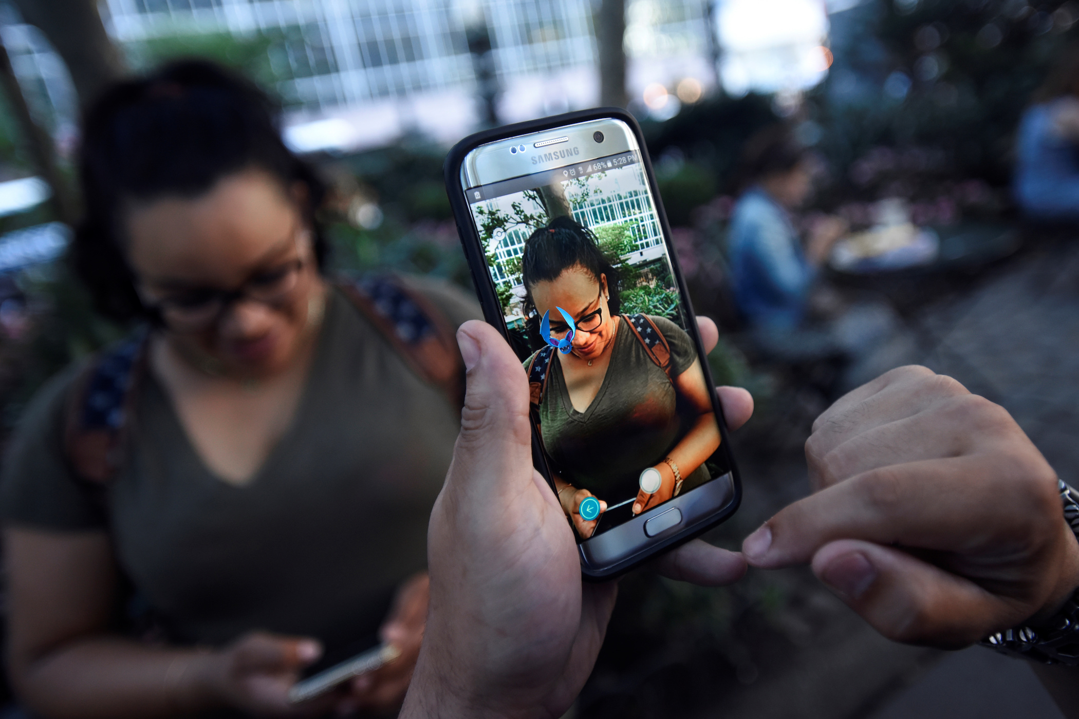 "A Pokemon appears on the screen next to a woman as a man plays the augmented reality mobile game ""Pokemon Go"" by Nintendo in Bryant Park in New York City, U.S. July 11, 2016. REUTERS/Mark Kauzlarich"