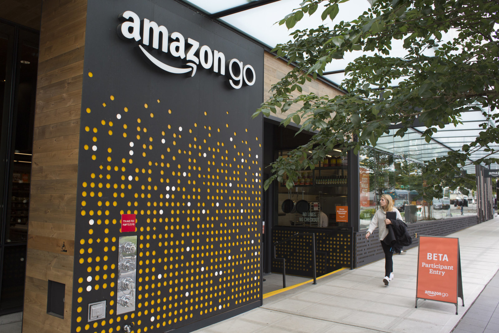 SEATTLE, WA - JUNE 16: A woman walks past the Amazon Go grocery store at the Amazon corporate headquarters on June 16, 2017 in Seattle, Washington. Amazon announced that it will buy Whole Foods Market, Inc. for over $13 billion.  (Photo by David Ryder/Getty Images)